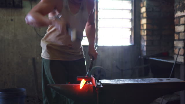 Blacksmith forging hot iron on anvil in his workshop