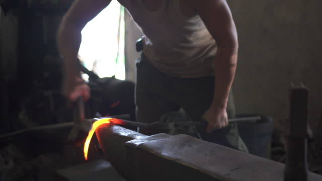 Blacksmith forging hot iron on the anvil