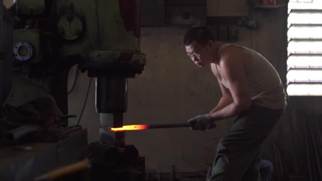 blacksmith forging iron in his workshop - artigianato video stock e b–roll