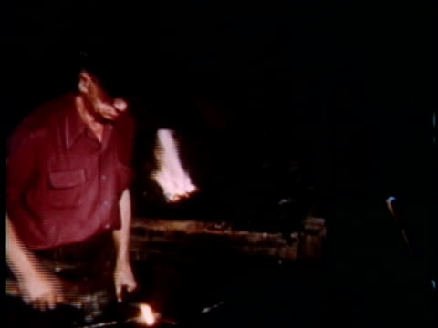 1951 ms blacksmith hammering at his forge, fire blazing behind him / detroit, michigan, united states - blacksmith stock videos and b-roll footage