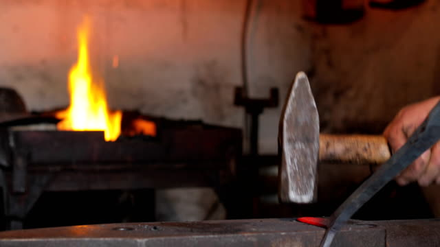 Blacksmith Hammering Heated Iron in his Forge