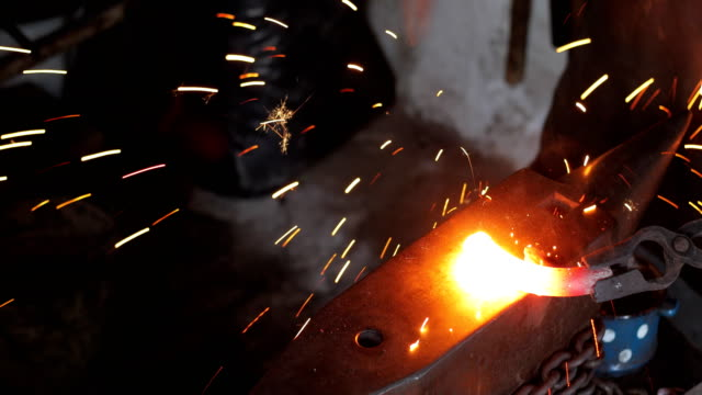 blacksmith hammering heated iron on anvil - hammer stock videos and b-roll footage
