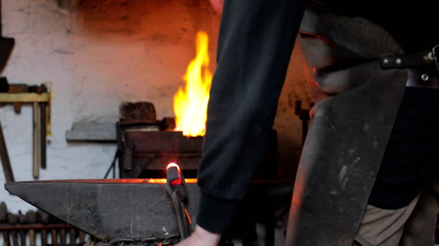Blacksmith Hammering Heated Iron on Anvil