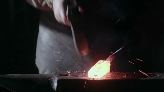 a blacksmith hammers on a red-hot block of steel before setting the hammer down and brushing away debris from his workbench, uk. - rhythm stock videos and b-roll footage