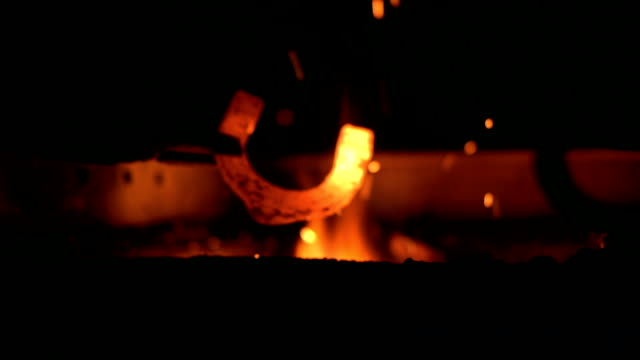 hd: blacksmith heating a horseshoe - horseshoe stock videos and b-roll footage