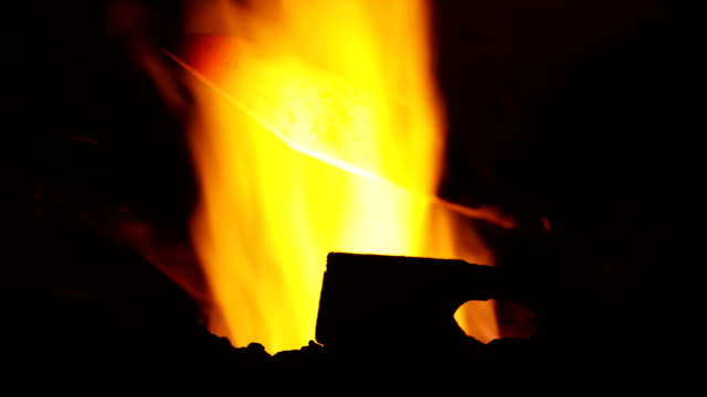 blacksmith holding a glowing heated knife over fire - knife weapon stock videos & royalty-free footage