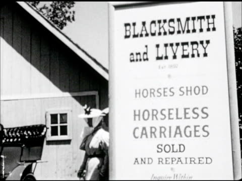 'blacksmith livery horses shod horseless carriages sold and repaired' sign pan ws man woman w/ salesman all in period clothing looking at motor... - 20世紀のスタイル点の映像素材/bロール