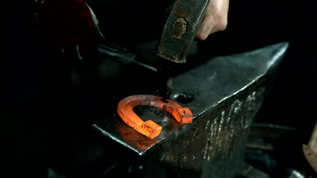 hd: blacksmith making holes in a horseshoe - horseshoe stock videos and b-roll footage