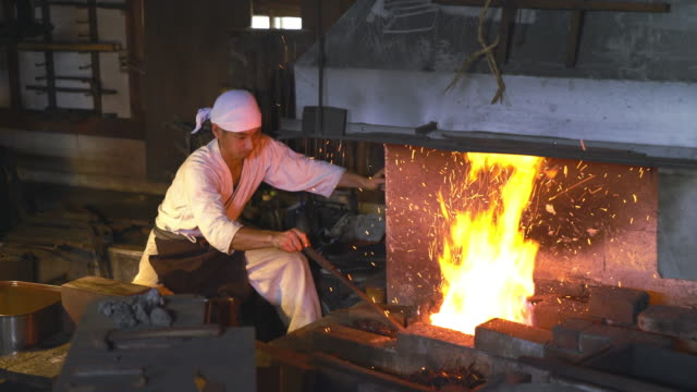 Blacksmith pumping the bellows of his furnace