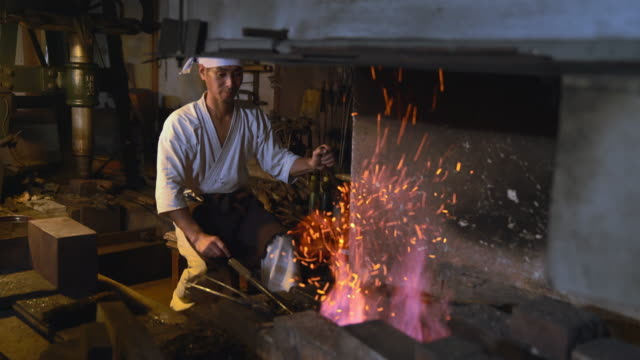 Blacksmith pumping the flames in his furnace
