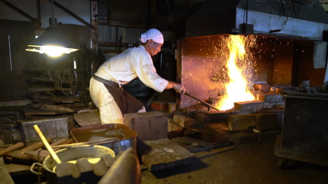 vídeos de stock e filmes b-roll de blacksmith removing metal from furnace and using a hammer to shape it - samurai