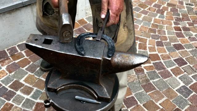 blacksmith shapes a horseshoe - ferro di cavallo accessorio per animali video stock e b–roll