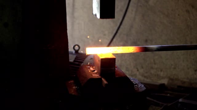 blacksmith shaping a piece of iron with hydraulic press machine - blacksmith stock videos & royalty-free footage