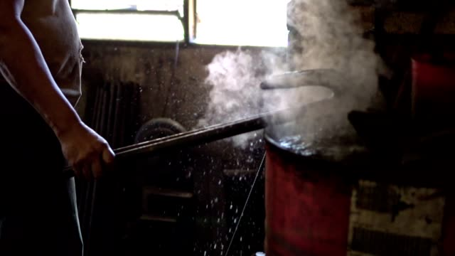 Blacksmith shaping an iron with hammer