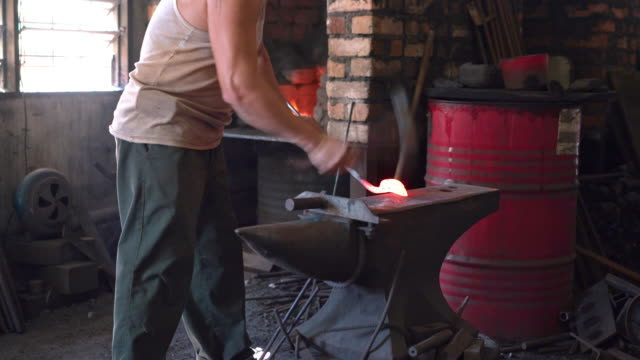 Blacksmith shaping metal on anvil and puts it in a forge