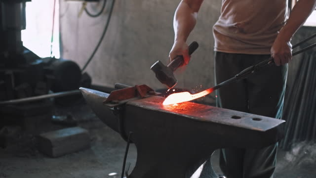 blacksmith shaping metal on anvil - hammer stock videos and b-roll footage