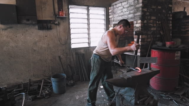Blacksmith shaping metal on anvil