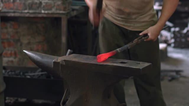 Blacksmith shaping metal with hydraulic press machine and hammer on anvil