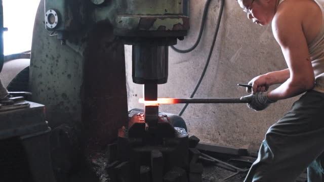 Blacksmith shaping metal with hydraulic press machine