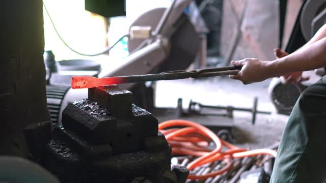 Blacksmith shaping metal with hydraulic press machine