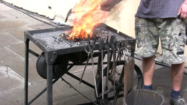 (hd1080i) blacksmith stoking flames - human limb stock videos & royalty-free footage