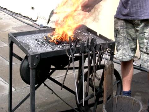 Blacksmith Stoking Flames