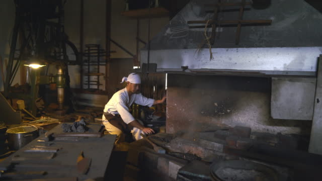 vídeos de stock e filmes b-roll de blacksmith stoking the flames of his furnace - samurai