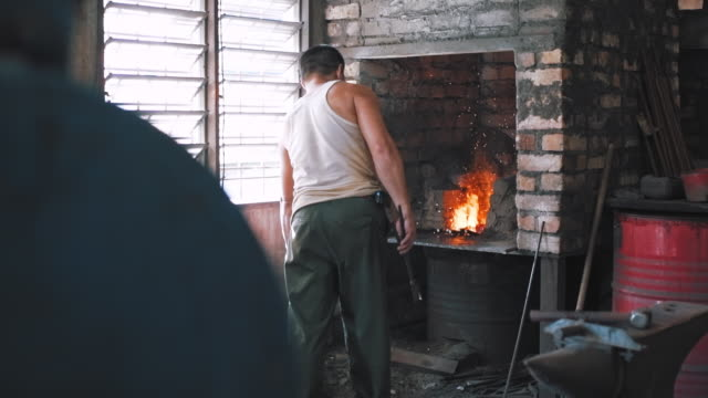 blacksmith taking iron rod from the fire - rod shape stock videos & royalty-free footage