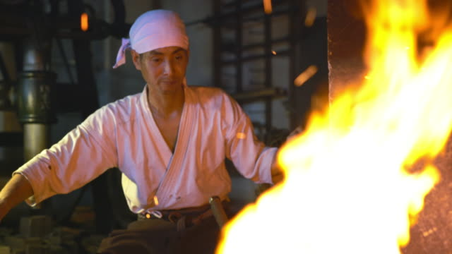 blacksmith through the flames of his furnace - blacksmith stock videos & royalty-free footage