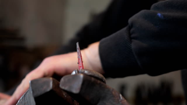 Blacksmith Twisting and Designing Heated Iron