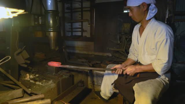 金属の形状にハンマーを使用して鍛冶屋 - 作業場点の映像素材/bロール