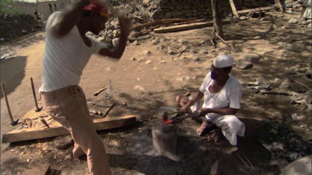 MS ZI CU Blacksmiths working outdoors pounding hot metal with hammers, Pune, Maharashtra, India