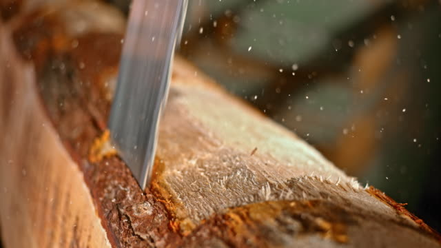 slo mo blade of vertical saw cutting a log - industria forestale video stock e b–roll