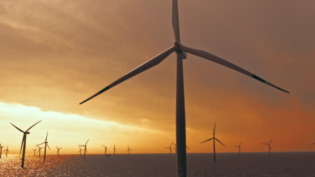 vídeos de stock, filmes e b-roll de lâminas aéreas da turbina de vento a pouca distância do mar que giram no por do sol - energia eólica