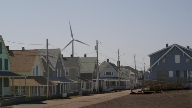 ws blades of wind turbine spinning near houses on residential street / hull, massachusetts, usa - turbine stock videos & royalty-free footage