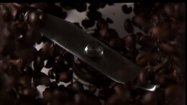 blades spin in a coffee grinder. - bean stock videos & royalty-free footage