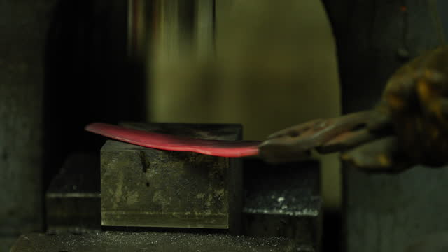 bladesmith working with hot blade at hydraulic forge hammer - one mid adult man only stock videos & royalty-free footage