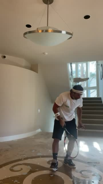 blair is inside his house in hollywood, california holding a tennis racket and practicing his swing. he accidentally hits and breaks the chandelier... - tennis racket stock videos & royalty-free footage