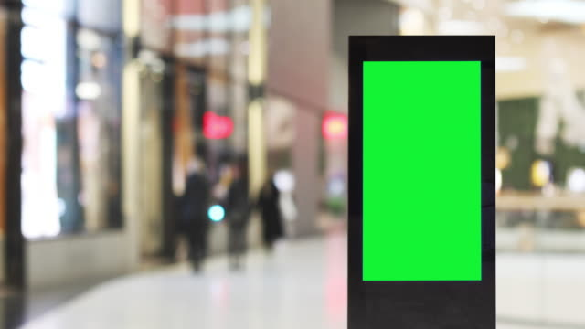 blank electronic billboard in a shopping arcade with stores - tabellone video stock e b–roll