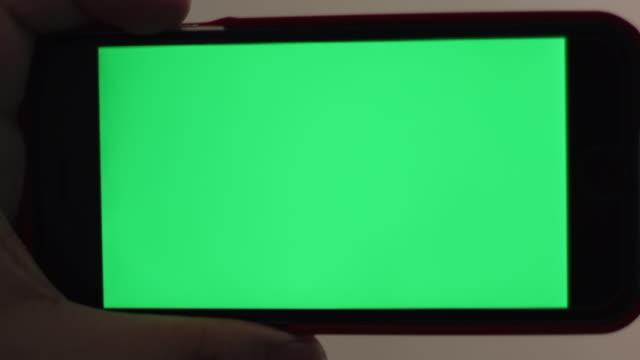 vidéos et rushes de téléphone intelligent écran vert blanc se bouchent avec la main - écran tactile
