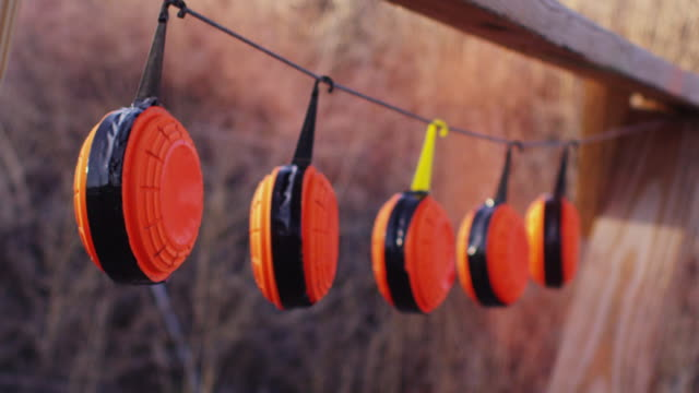 blaze orange clay pigeon rifle targets hang at a shooting range, exploding when hit with a bullet. - clay pigeon shooting stock videos & royalty-free footage