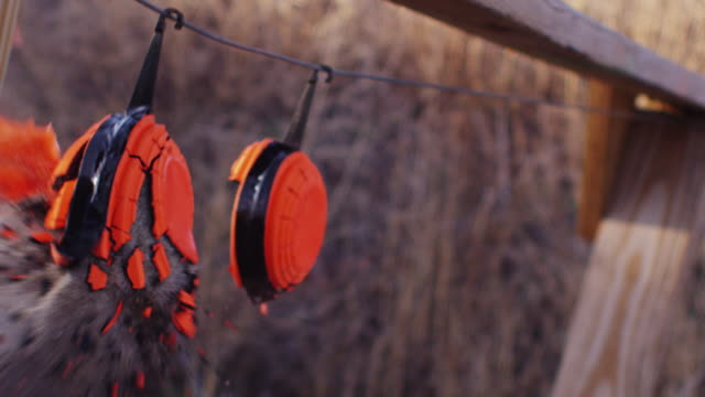 blaze orange clay pigeon rifle targets hang at a shooting range, exploding when hit with a bullet. - clay pigeon shooting stock videos and b-roll footage