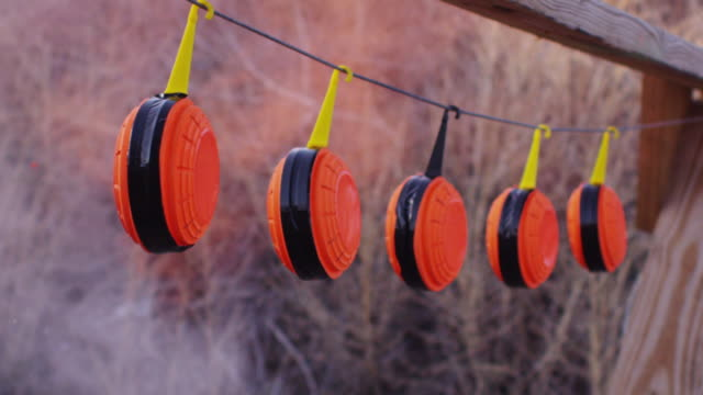 blaze orange clay pigeon rifle targets hang at a shooting range, exploding when hit with a bullet. - tiro al piattello video stock e b–roll
