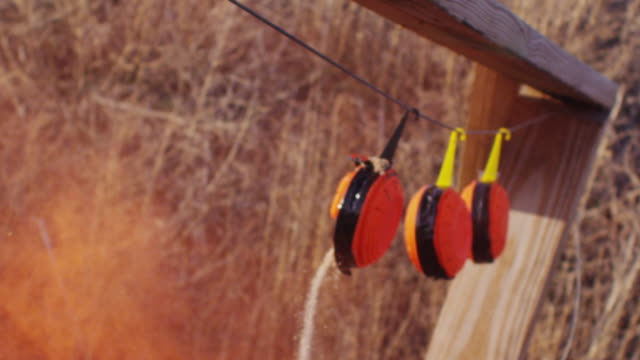 blaze orange clay pigeon shooting targets dramatically explode when shot with bullet from a rifle. - tiro al piattello video stock e b–roll