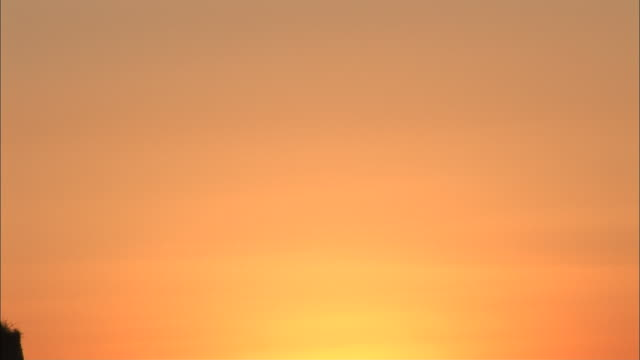 a blazing sun casts orange light across the sky. - dusk stock videos & royalty-free footage