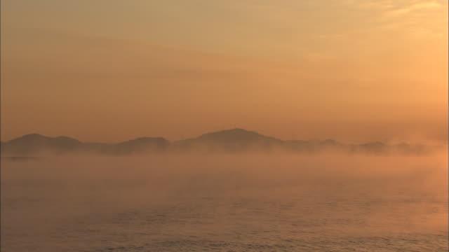 A blazing sun glows above the foggy Inland Sea.