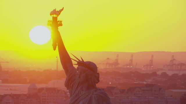 a blazing sun glows above the statue of liberty in new york city. - statue of liberty new york city stock videos & royalty-free footage