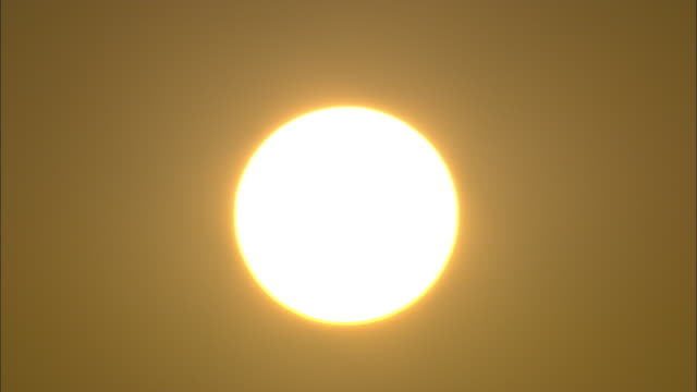 A blazing sun glows in a hazy sky.