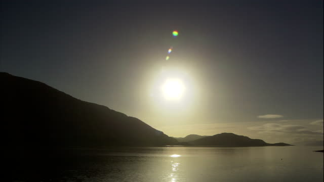 stockvideo's en b-roll-footage met a blazing sun glows over a mountainous coast in oban, scotland. - astronomie