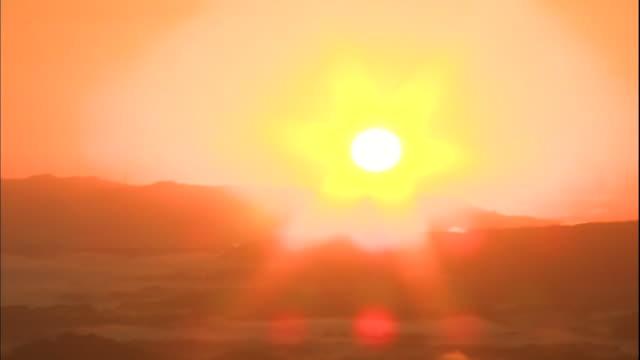 vidéos et rushes de a blazing sun rises above the kirishima mountains and a dense sea of clouds. - inclinaison vers le bas